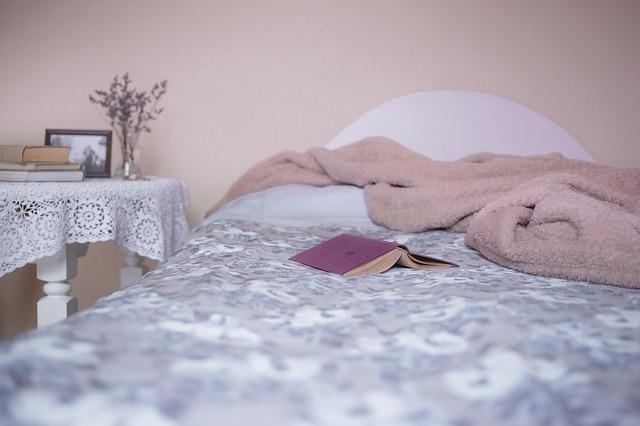 postel s hnědým přehozem, stolkem a fialovou knihou